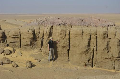 Fig.5 : Grand yardang composé de sédiments fins apportés par le vent. La couche très différente constituant son sommet est composée des déblais de creusement d'un regard de qanat à l'époque ptolémaïque ou romaine. La hauteur du dépôt que ces déblais ont protégé de l'action du vent témoigne donc de la hauteur des terres cultivées et habitées durant l'antiquité.